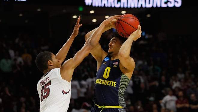 South Carolina's PJ Dozier (left) defends against Markus Howard.