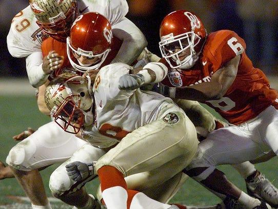 Oklahoma quarterback Josh Heupel (14) gets crunched