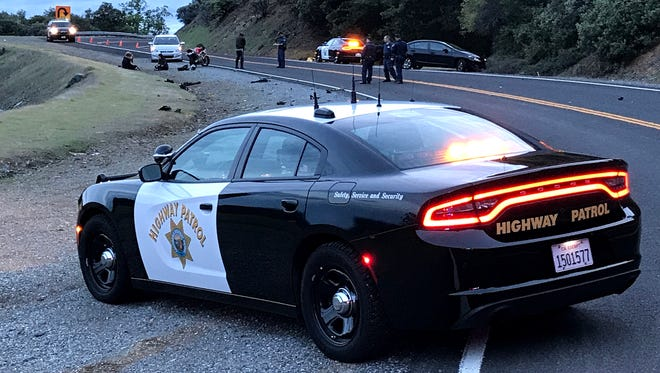 California Highway Patrol officers investigate a fatal crash between a motorcyclist and a bicyclist Tuesday evening on Highway 151, which leads from the city of Shasta Lake to Shasta Dam.