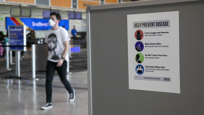 """Sam Pierce wears a mask while walking past an Austin Public Health sign at Austin-Bergstrom International Airport on Thursday March 12, 2020.  Pierce said he came to the airport in person to cancel his planned trip to Los Angeles.  He said he wore the mask as a precaution against catching coronavirus at the airport.  """"I feel like if I could get it anywhere I could get it here,"""" he said."""