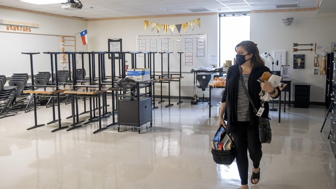 Tamra Franklin, an English teacher at Westwood High School, takes some of her belongings out of her classroom in May. The decision on when to reopen schools for in-person classes ultimately rests with local health departments.