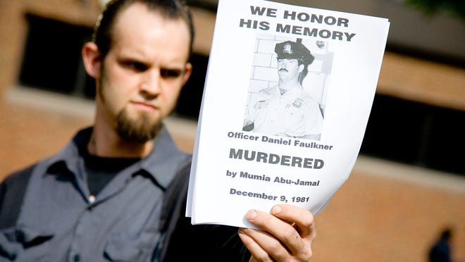 A protester holds a handbill in remembrance of slain police officer Daniel Faulkner in Philadelphia in 2007.