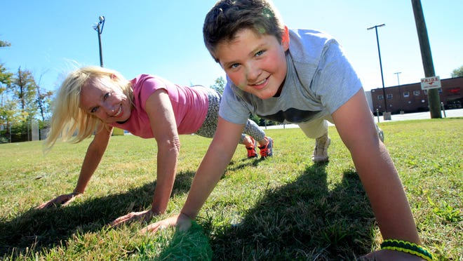 C-J columnist Kirby Adams, left, was challenged by Jack Chauvin, a student at St. Margaret Mary School, to the 90-second Pushup Challenge.