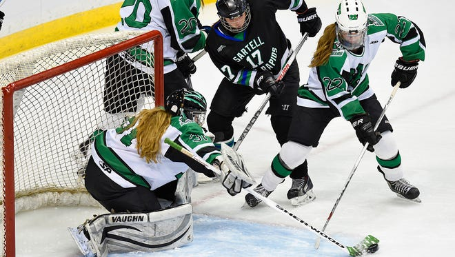 Sartell/Sauk Rapids' Molly Mahowald (17) takes a shot at the goal but the puck is swept away by Hill-Murray goalie Mari Johnson and Abigail Boreen (22) during the first period of the Class 2A quarterfinal Thursday, Feb. 18 at the Xcel Energy Center in St. Paul.