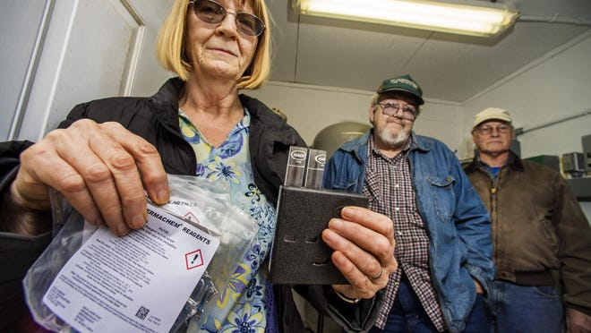 Marjorie Archer, from left, Bob Archer and Iver Bjerke of the Wildwood West Homeowners Association at the development's pump house in Charlotte on Thursday, April 7, 2016. The residents are responsible for testing their own water. Marjorie Archer is holding one of the testing kits she uses.
