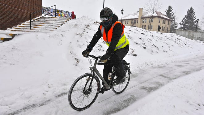 A bundled up cyclist pedals across the University of Vermont campus in February 2015. The National Weather Service is forecasting what may be the coldest temperatures this winter during the upcoming weekend.