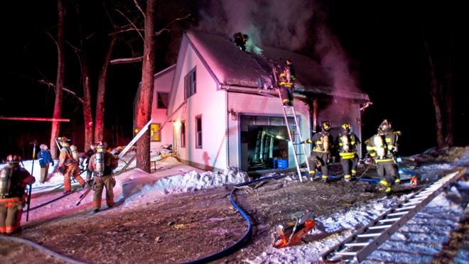 Firefighters from several local departments battle a garage fire at a home on Lyman Drive in Williston on Thursday.