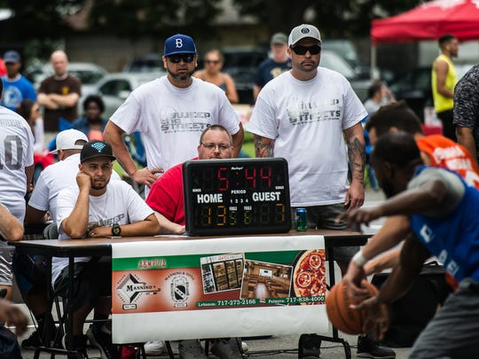 From left,  co-founders George Rodriguez (sitting), Angel Cruz and Robert Cleapor (both standing) watch the game between Eisenhauer and Himmy's during the 10th annual Sweep the Streets basketball tournament on Saturday at Southeast Playground.