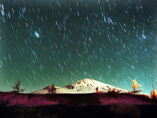 Leonid meteors streak across the sky over snow-capped Mount Fuji, Japan's highest mountain, on Nov. 19, 2001.