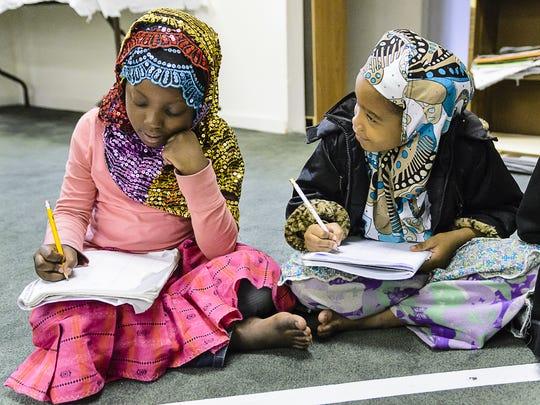Fatima Mberwa (left), 6, and Zaituh Mussa, 5, study