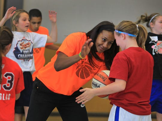 Tamika Catchings, center, laughs with kids while trying to steal the ball in ball handling drills during the Tamika Catchings' Catch the Stars Foundation 13th Annual Youth Holiday Basketball Camp at Warren Central High School, Friday, December 27, 2013.  The 7-time WNBA All-Star, 3-time Olympic Gold Medalist, 2011 WNBA MVP, 2012 WNBA finals MVP, and the 5-time Defensive Player of the Year host the holiday camp this weekend for about 250 kids.  She hopes this becomes THE camp for the holiday, giving kids something great to do during their holiday break.