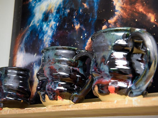 Joel Cherrico shows some of his work in a collection of cosmic mugs Friday, March 25, at his studio in St. Joseph.