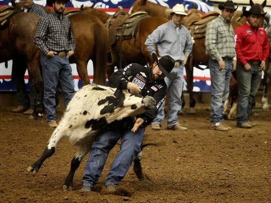 Luke Branquinho wrestles down a steer during the Steer Wrestling competition on Day 1 of Slack Tuesday, February 7, 2017. Branquinho tied third with Ty Erickson, Blake Knowles and Justen Notes with 3.5 seconds each.