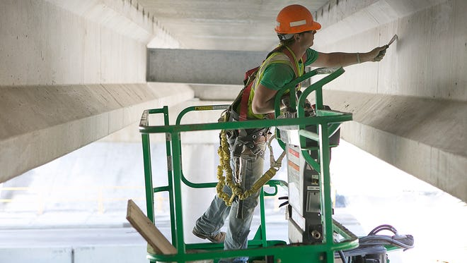 Cody Rosemeyer smooths the concrete underneath an overpass that is under construction near Mosinee.