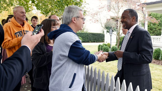 Republican presidential candidate Dr. Ben Carson, right, shake hands with supporters on the sidewalk in front of the home of the City of Franklin Mayor Ken Moore where Moore hosted a fundraiser for Carson on Saturday, Oct. 31,  2015.