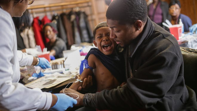 Mike Henry Sr. holds his grandson Kaiden Olivares, 3, as he screams while giving a blood sample to be tested for lead on Saturday, Jan. 23, 2016, at the Masonic Temple in downtown Flint, Mich. A CDC report released Friday, June 24, 2016, found that blood-lead levels among children jumped dramatically after Flint switched water to the Flint River.
