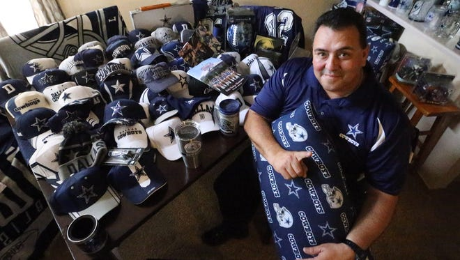 Avid Dallas Cowboys fan Jaime Garcia shows part of his cap collection and other memorabilia in his East El Paso home.