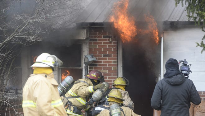 Richmond firefighters prepare to enter an abandoned house to extinguish a fire set for a video shoot.