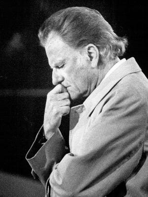 The Rev. Billy Graham prays while visiting Rochester in this 1988 photo.
