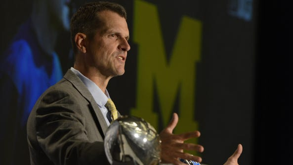Michigan coach Jim Harbaugh speaks to the media during