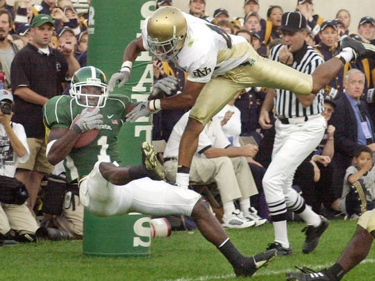 Michigan State receiver Charles Rogers (1), defended by Notre Dame cornerback Shane Walton, lands with one foot in the endzone for a touchdown at Spartan Stadium in East Lansing, Sept. 21, 2002.