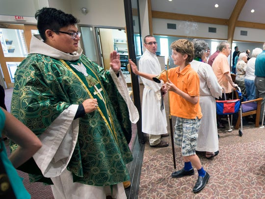 Co-pastor Rev. Ben Erzkus, left, high-fives acolyte Zachary Smith, 12, at Zion Lutheran Church in Manchester Township, after Zachary extinguishes the candles concluding the first service.