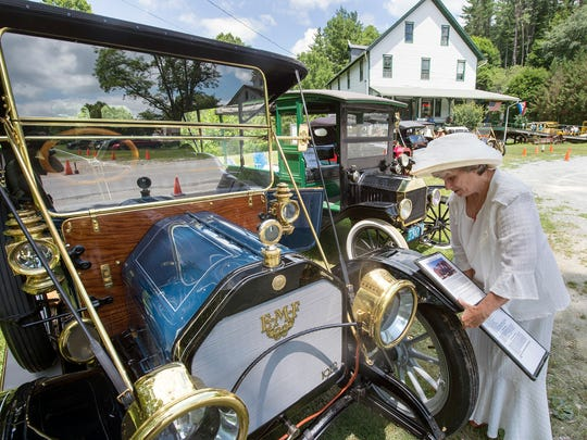 """Betty Swan of Wrightsville places information on a 1912 E-M-F during Early American Auto Day at the Ma & Pa Railroad Heritage Village at Muddy Creek Forks. Betty and her husband, Joe, drove the E-M-F 10,750 miles cross-cross country in 2015, saying it """"was a trip of a lifetime."""" The trip included 900 miles in the desert. Swan said that the """"air-conditioning worked beautifully,"""" adding that there is a lot of cross ventilation as long as you are moving."""