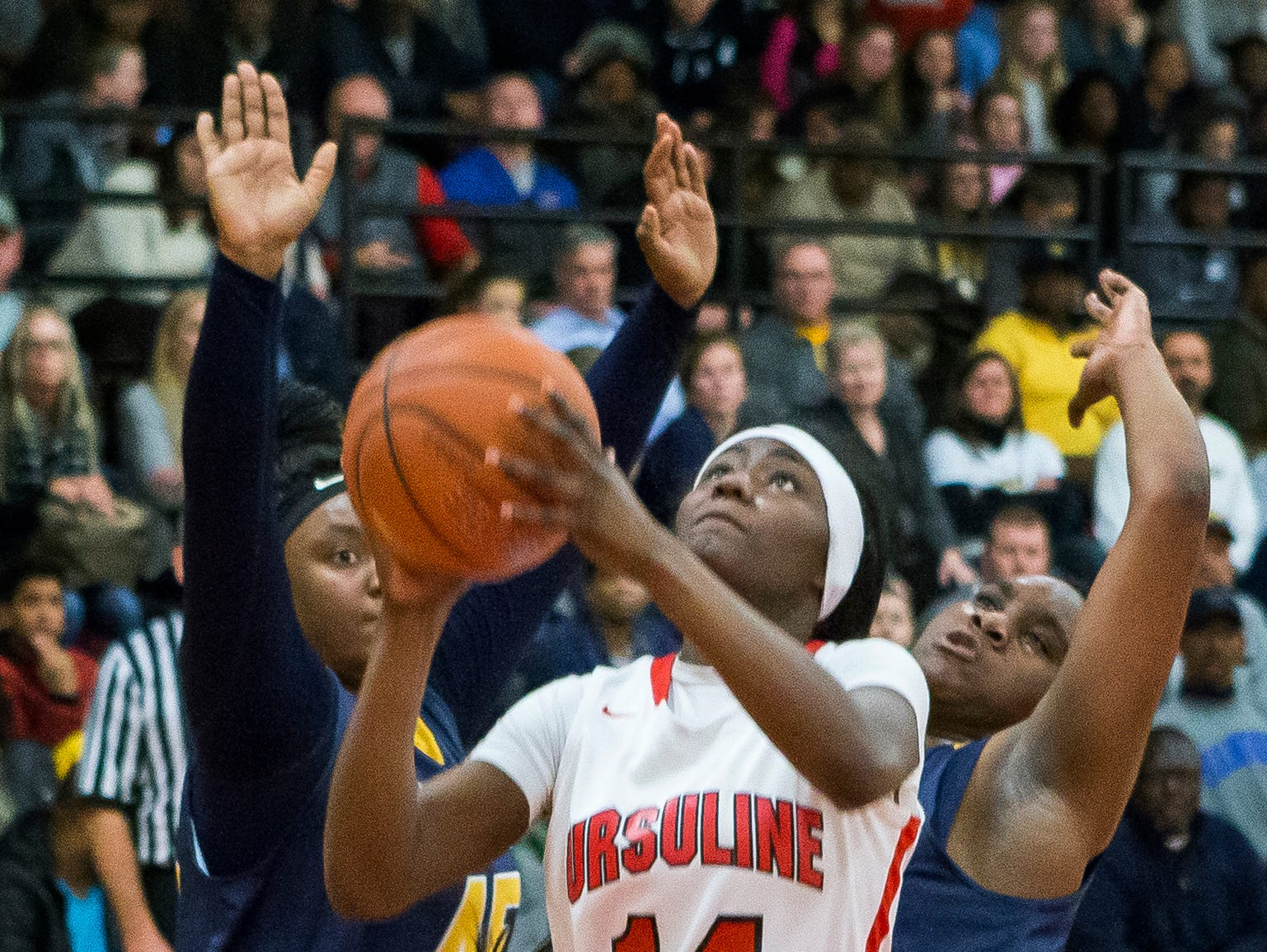 Ursuline's Kryshell Gordy (No. 14) puts up a shot in front of Sanford's Kendra Warren (No. 45) and Samantha Pollich in the second half of Ursuline's 50-40 win over Sanford at Ursuline Academy on Thursday night.