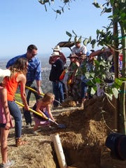 Ventura City Council member Matt LaVere helps shovel in dirt with his wife, Alicia, and daughter Lucia.