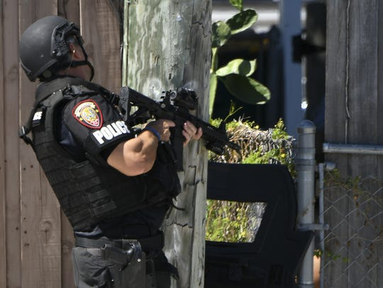 An officer in tactical gear peers through a hole in