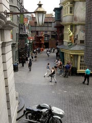 People walk along Diagon Alley during a preview at the Wizarding World of Harry Potter at Universal Orlando, Thursday, June 19, 2014, in Orlando, Fla.