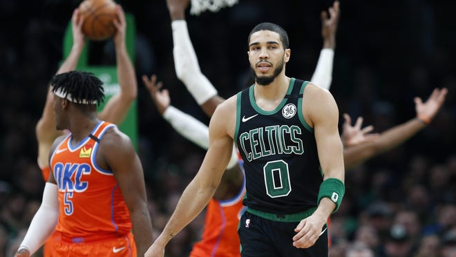 In this March 8, 2020, file photom, Boston Celtics' Jayson Tatum (front) walks on the court during the second half of an NBA basketball game against the Oklahoma City Thunder in Boston. Jayson Tatum and the Celtics were rusty in their first srimmage in Orlando against the Oklahoma City Thunder.