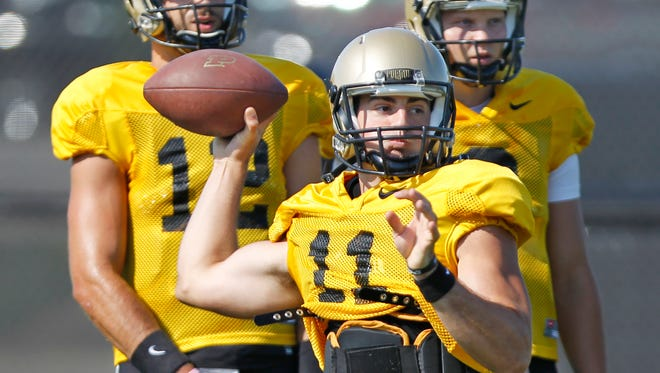 Quarterback David Bloug with a pass during football practice Thursday, August 20, 2015, at Purdue University. Looking on are quarterbacks Austin Appleby, background left, and Elijah Sindelar.
