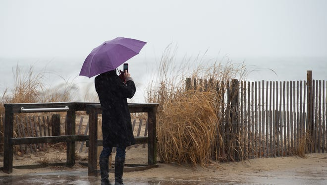 A beachgoer takes photos of the waves at Rehoboth Beach.