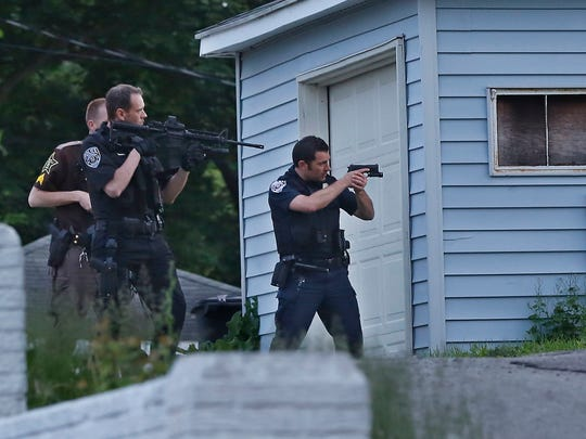 Police officers secure the scene where a fugitive was holed up in a house in the 1000 block of S. Third Street Saturday, May 16, 2015, in Lafayette. Shortly after 11 p.m. Marcus Alan Bramlett, 25, an inmate at the Tippecanoe County Jail who stole a Tippecanoe County Sheriff's Office squad car Friday, surrendered to police without incident.