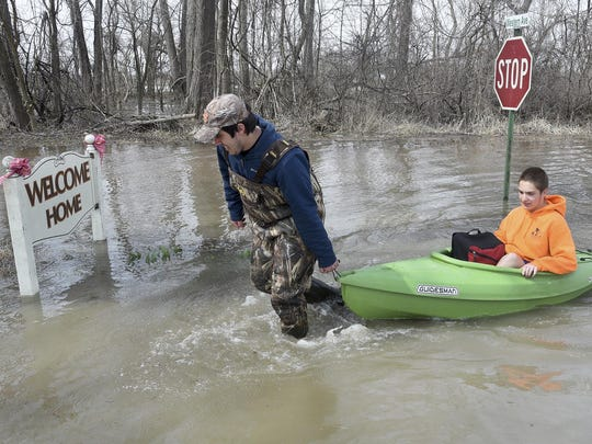 Louis Flory gets his younger brother Levi Flory, a ninth grader at Monroe Middle College at MCCC, after school Thursday, April 11, 2019 using a canoe to take him home in North Shores, LaSalle, Mich. The water was not even over the road when Levi went to school Thursday morning.