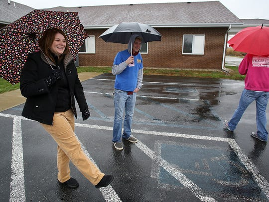 Democrat Melanie Wright seems to be dancing in the rain outside the polling place at University Christian Church, Yorktown, on Tuesday afternoon.