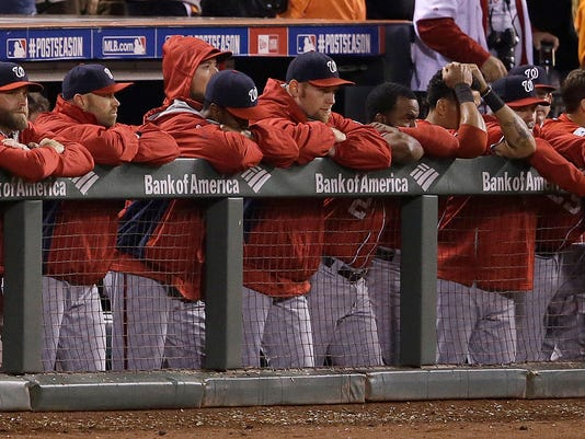 Washington Nationals players lean on the dugout fence during the ninth inning of Game 4 of baseball's NL Division Series against the San Francisco Giants in San Francisco, Tuesday, Oct. 7, 2014. The Giants won 3-2 to win the series. (AP Photo/Jeff Chiu)