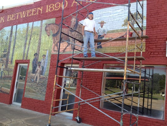 Artist Fred Stark stands on scaffolding in front of