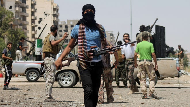 Syrian rebels fighting pro-regime forces gather along a road in Syria's eastern town of Deir Ezzor last week.