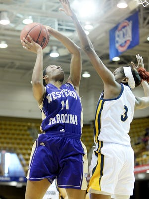 Western Carolina's Sherae Bonner attempts to shoot as Chattanooga's Jasmine Joyner reaches to block in the first round of the Southern Conference Tournament March 2, 2017 at the US Cellular Center in Asheville.