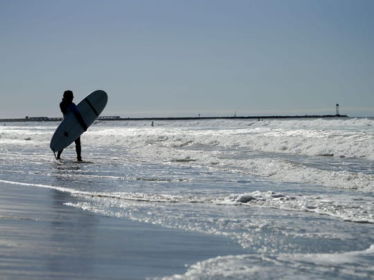 Harmony Lallo, from Franktown, Colorado, tries her hand at surfing in San Diego. San Diego's coast boasts world-class surfing but also decent waves for the novice.