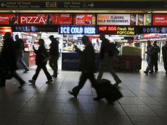This 2013 photo shows evening rush hour commuters making their way past the food concessions inside New York's Penn Station. Restrictions are still in place for trains in and out of New York's Penn Station as Amtrak workers repair a 300-foot section of electrical cable that caused recent delays.