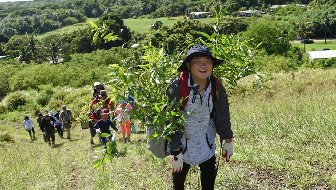 An exhausted Damon Yu, 12, cracks a smile for the camera during the Manell Watershed reforestation planting event in Merizo on Oct. 21, 2017.
