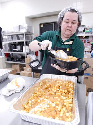 Penny Mercado makes canned yams with marshmallows as a pre-ordered Thanksgiving meal for customers at the Piggly Wiggly in Hartland.