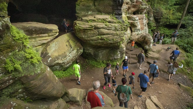 Visitors congregate around the cave structure along the Rock House trail in Hocking Hills State Park near Laurelville on Thursday. The trail reopened June 15 after being closed due to the coronavirus. Other tourism operations in rural Ohio are also beginning to welcome back visitors, reinvigorating an important industry but raising health worries.