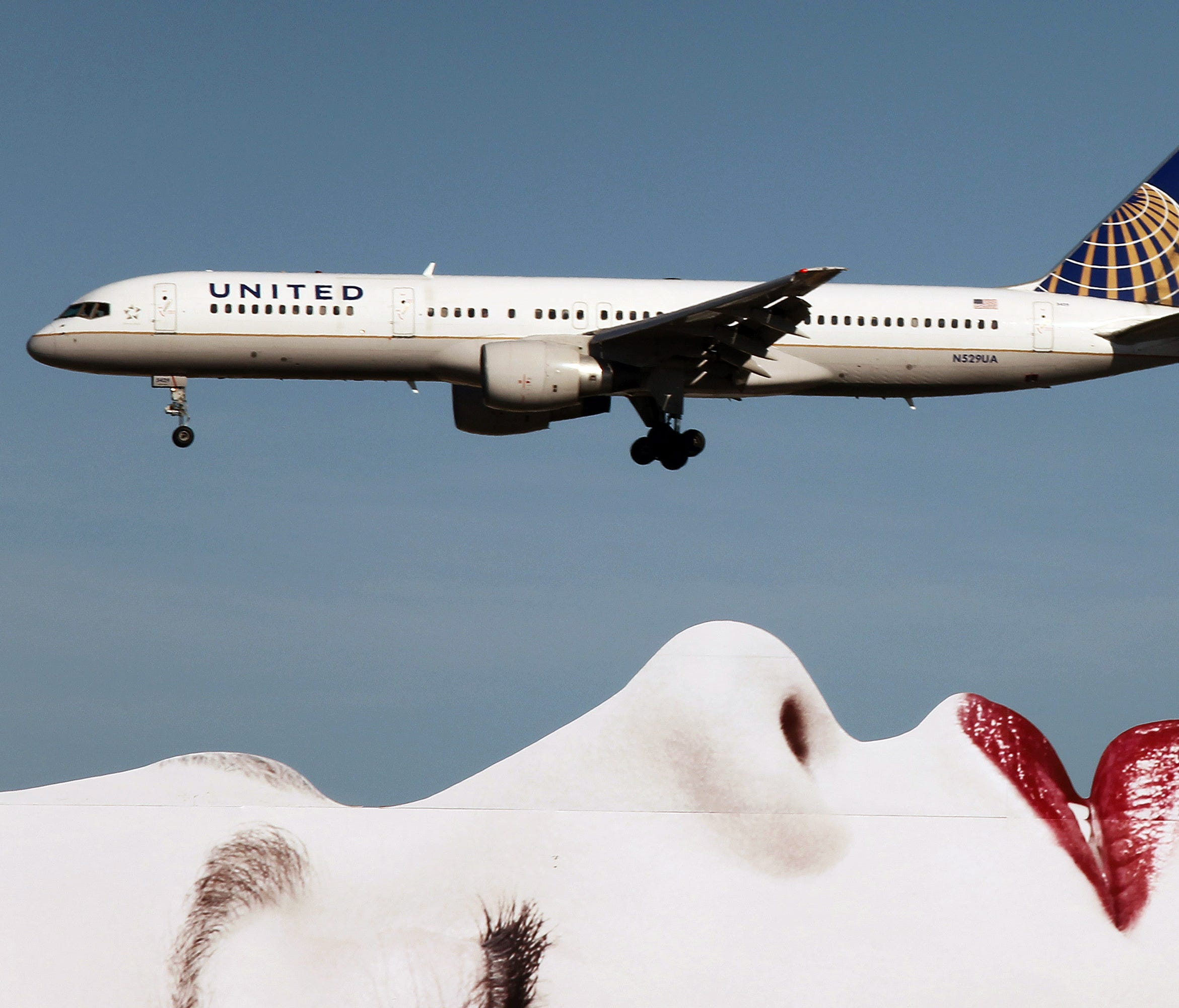 A United Airlines Boeing 757 passes a billboard on approach to Los Angeles International Airport (LAX) on Jan. 17, 2013.