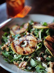 The Arugula salad at Amerigo has  flame-grilled apples, roasted walnuts, gorgonzola cheese and gorgonzola vinaigrette with grilled chicken or grilled salmon. This small local chain celebrates it's 20th anniversary this week, and owner Ben Brock can measure the success of his classic Italian eatery by the loyalty of his repeat customers.