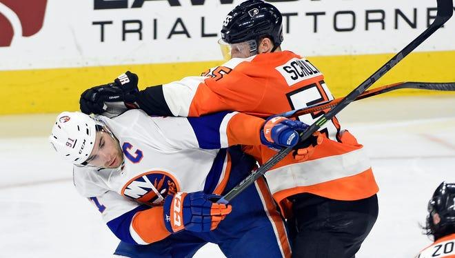 New York Islanders center John Tavares (91) and Philadelphia Flyers defenseman Nick Schultz (55) battle during the third period at Wells Fargo Center.