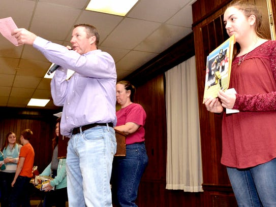 Auctioneer Tom Saylor and runner Kate Cramer auction